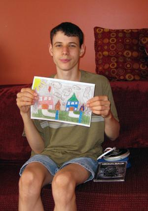 "Christian displays his crayon-and-pencil drawing, ""My Neighborhood,"" which was selected for an exhibit at the Arts Unbound museum in Orange for artists with disabilities. His artwork is a depiction of the SERV Achievement group home where he lives in East Windsor."