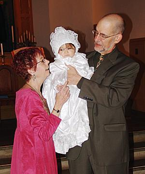 Helena's foster parents, Pat and Bob, hold MaryAnna during the baby's christening in March at the United Presbyterian Church in Plainfield.